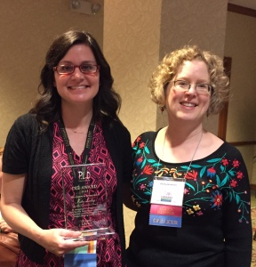 JCLI Executive Director Kate Lasky (left) holds her OLE award plaque with OLA Past President Penny Hummel.