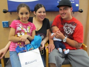The Ulloa family receives Baby's First Book through an Asante Three Rivers Medical Center partnership sponsored by Roe Motors.