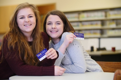 Photo of two teenaged girls, smiling and showing off their library cards.
